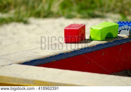 Childhood. Old Sandpit Sandbox With Colorful Plastic Blocks Toys On The Playground. Outdoor. Play. S
