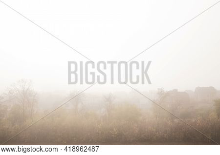 A Foggy Morning In A Village Landscape. Countryside Houses In Fog View. Peaceful Trees And Small Rur
