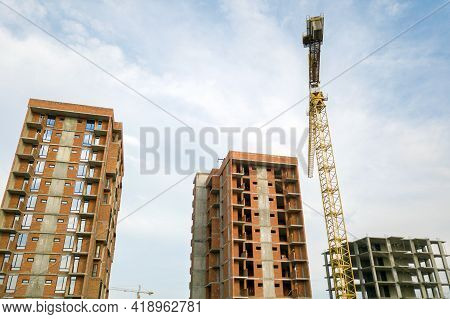 High-rise Residential Apartment Buildings And Tower Crane Under Development On Construction Site. Re