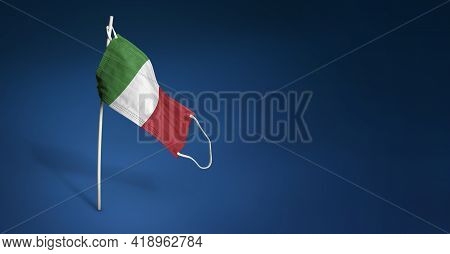 Italy Mask On Dark Blue Background. Waving Flag Of Italy Painted On Medical Mask On Pole. Concept Of
