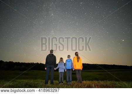 Happy Family Standing In Night Field Looking At Dark Sky With Many Bright Stars. Parents And Childre