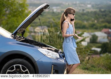 Upset Young Woman Driver Talking Angrily On Cell Phone With Assistance Service Near A Broken Car Wit