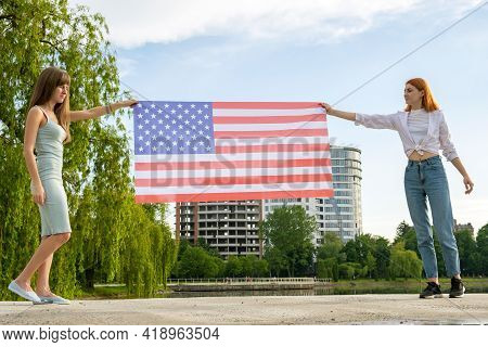 Two Young Friends Women Holding Usa National Flag In Their Hands At Sunset. Patriotic Girls Celebrat