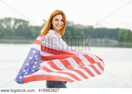 Happy Smiling Red Haired Girl With Usa National Flag On Her Shoulders. Positive Young Woman Celebrat