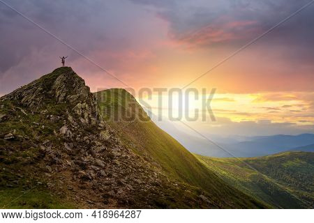 Small Silhouette Of Hiker Standing With Raised Arms On Rocky Mountain Top At Sunset.