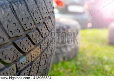 Winter Tires Close Up With Flare Effect. Self Replacement Of Winter Tires On A Car With Summer Wheel