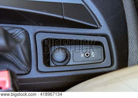 Auxilary Input Jack For 1/8 Inch Plug Is Modern Convenience On The Center Console Of Automobile.