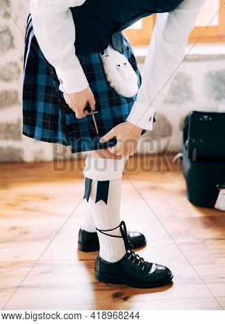Preparing For A Scottish Wedding. Man In High Socks, Sporran And Shoes With Long Laces Attaches A Sm