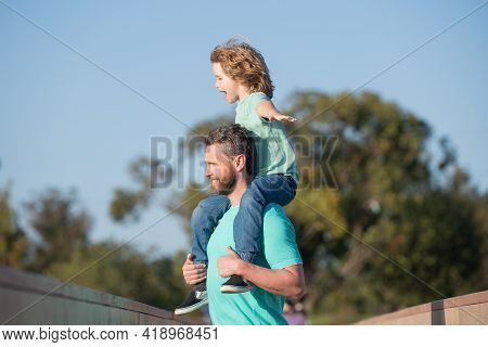 Daddy Piggyback His Little Son Outside. Handsome Father Piggybacking Son Playing On Nature, Dad Hold