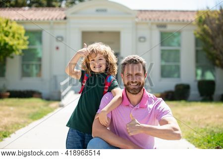 Portrait Of Parent And Pupil With Thumbs Up Of Primary School Go Hand In Hand. Teacher In T-shirt An
