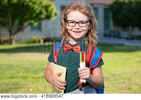 Smiling School Student Wit Backpack Book. Portrait Of Happy Pupil Outside The Primary School. Closeu