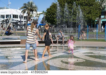 Tauranga New Zealand - April 3 2021; Couple And Child Enjoy Dodging Water Spurts In Waterfront Water