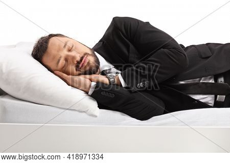 Businessman in a suit and tie sleeping on a bed peacfully isolated on white background