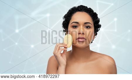 beauty, people and skincare concept - young african american woman with bare shoulders cleaning face with exfoliating sponge over low poly hologram on grey background