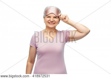 old people concept - portrait of smiling senior woman in pajamas and eye sleeping mask over white background