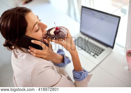 A young handsome business woman is enjoying while eating a delicious donut with a pleasure and talking on a phone in a pleasant atmosphere in a pastry shop. Pastry shop, dessert, sweet