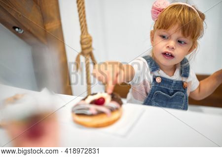 A little girl in a pastry shop is amazed by delicious donut of irresistible appearance. Pastry shop, dessert, sweet