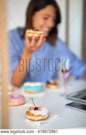A happy young woman is eating delicious donuts in a pleasant atmosphere in a pastry shop. Pastry shop, dessert, sweet