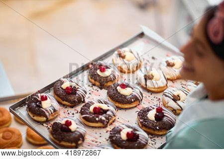 Close up of a tray full of handmade delicious donuts of irresistibility appearance ready for a pastry shop hold by a happy small busines female owner. Pastry, dessert, sweet, making