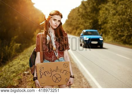 Pretty hippie girl hitchhiking along a road. Spirit of freedom. Summer vacation adventure.
