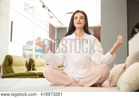 Beautiful brunette girl in a white shirt meditates sitting in the lotus position on a bed in her cozy studio apartment. Home interior, furniture. Healthcare.