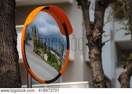Road Round Mirror. Mirror To Help Transport. Help Cornering. Red Round Mirror On A Post. Road Mirror