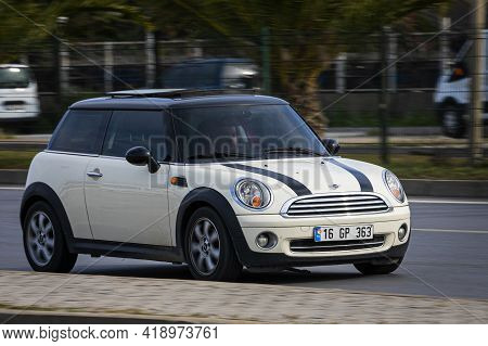 Alanya, Turkey - April 16 2021: White Mini Cooper   Is Driving Fast On The Street On A Warm Summer D