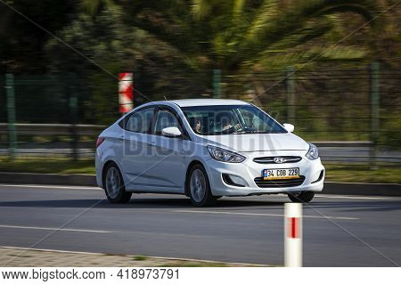 Alanya, Turkey - April 16 2021:   White Hyundai Solaris  Is Driving Fast On The Street On A Warm Sum