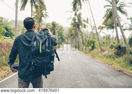 Rear View Of Man With Backpack Hiking And Walking On The Road In Forest. Backpack Travel Concept.