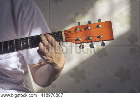 Sunlight And Shadow On Surface Of Teenage Boy Hand Practicing To Play The Guitar At Home