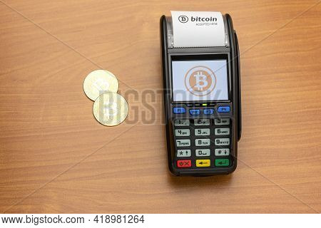 Payment Terminal Ready To Accept Bitcoins For Payment. There Are Bitcoin Coins On The Table Nearby