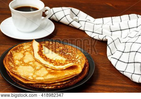 Thin Pancakes On A Plate. Wooden Background.