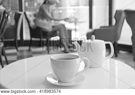 Monochrome Porcelain Teacup And Pot On A Round Table In A Cafe