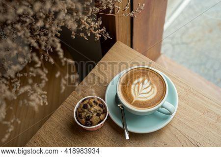 Hot Coffee Latte With Latte Art Milk Foam In Cup Mug And Homemade Banana Cup Cake On Wood Desk On To