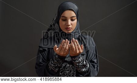 Pretty Young Arabian Woman Wearing Traditional Hijab And Looking At Her Palms On Dark Background, Wi