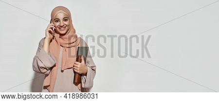 Happy Young Arabian Girl In Hijab Talking On Smartphone While Posing On Light Background And Smiling