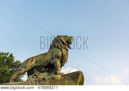Bronze Lion Statue Against A Clear Sky At Dusk In Madrid, Spain.