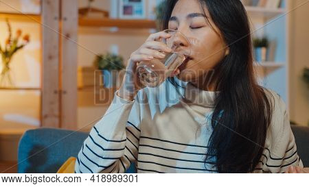 Sick Young Asia Woman Holding Pill Glass Of Water Take Medicine Sit On Couch At Home Night. Girl Tak