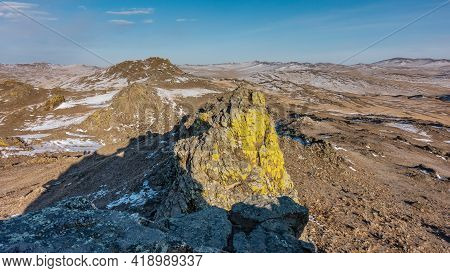 Mountainscape. Mountains, Devoid Of Vegetation, Rise Above The Bare Ground. Yellow Lichens Grow On T