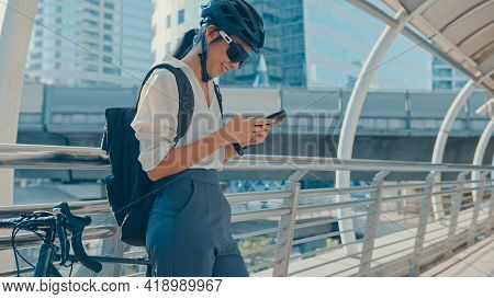 Happy Asian Businesswoman With Backpack Use Smart Phone In City Stand At Street With Bike Go To Work