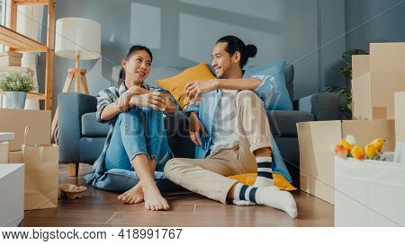 Happy Asian Young Attractive Couple Man And Woman Sit At New Home Drink Coffee Relax And Talk Smile