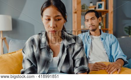 Upset Asian Couple Wife Sit On Couch Listen To Furious Husband Yelling Feel Unhappy Talk Negative To