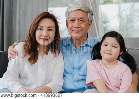 Asian Grandparents Watch Tv With Granddaughter At Home. Senior Chinese, Grandfather And Grandmother
