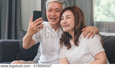 Asian Senior Couple Video Call At Home. Asian Senior Chinese Grandparents, Using Mobile Phone Video