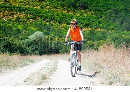 mountain biker on sunny day against forest