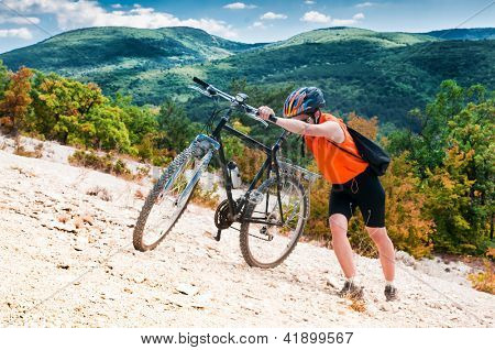 female cyclist raises his mountain bike on the mountain