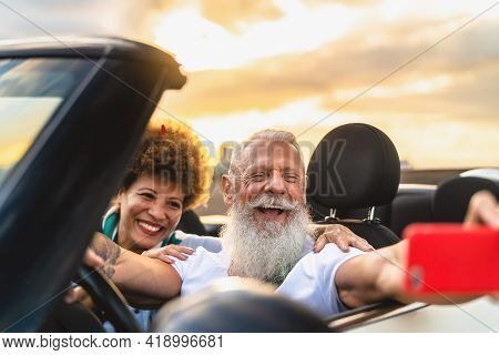 Happy Senior Couple Having Fun On New Convertible Car Roadtrip Taking Selfie With Mobile Smartphone