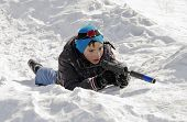 boy in winter clothes with a machine gun to play laser tag lying in the snow poster