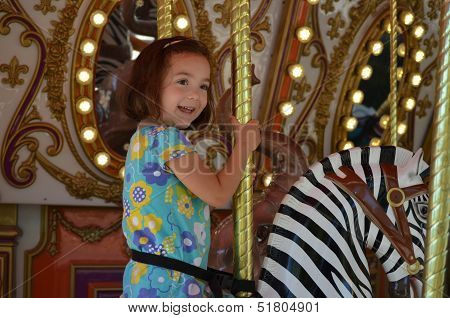 Happy Little Girl Riding A Carousel