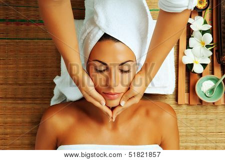 portrait of young beautiful woman getting a massage on colored background. poster